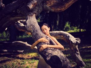 Young woman in nature between trees and tree trunks