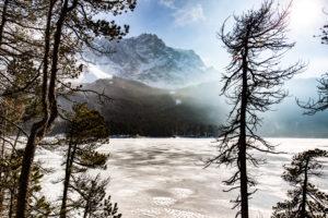 Der zugefrorene Eibsee vor der Zugspitze in Deutschland. Blick durch die Bäume.