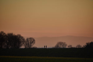Two people in the distance on a dirt road in the sunset glow