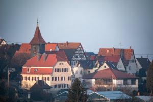 Der Kern vom Stadtteil Stuttgart-Heumaden mit Blick auf die alte evangelische Kirche, dem Pfarrhaus und dem ältesten Haus Heumadens.