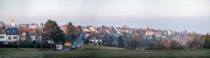 Panorama vom Stadtteil Stuttgart-Heumaden mit Blick auf die alte evangelische Kirche, dem Pfarrhaus und dem ältesten Haus Heumadens (rechts). Links im Bild die katholische Thomas-Morus-Kirche.