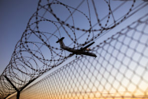 Airplane in the blue sky over a barbed wire fence