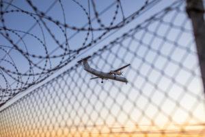 Flugzeug im blauen Himmel über einem Stacheldrahtzaun