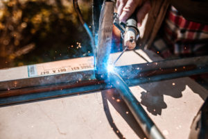 Arc welding on a workpiece with flying sparks, hobby craftsmen