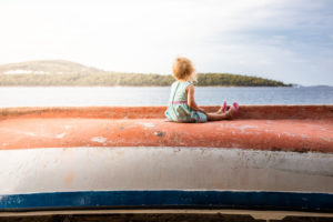 Little girl on an upturned boat looking out to sea. The face is not visible.