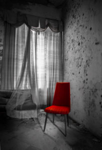 empty red chair by the window in an abandoned house