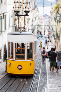 Paved narrow street canyon with tram, view down to the Tagus