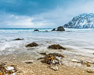 frozen sandy beach with running water