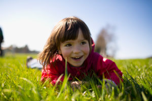 5-year-old girl lying with red jacket on a green meadow