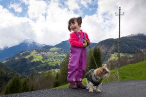 4-6 jähriges Mädchen mit mit Regenhose und Hund steht lachend am Straßenrand