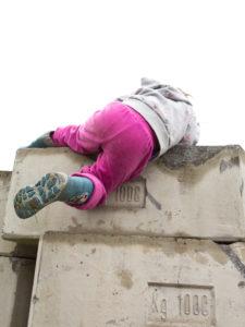 4-6 jähriges Kind mit pinker Hose klettert über Betonsteine