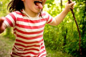 4-6 jähriges Kind mit Streifenhemd und Stock in der Hand rennt durch den Wald, Nahaufnahme, Detail,