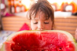 4-6 jähriges Kind schaut in ausgelöffelte Melonenschale im Wohnwagen