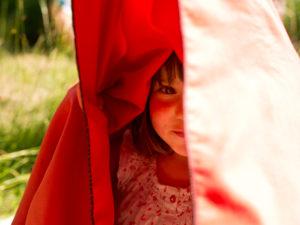 4-6 jähriges Mädchen unter rotem Badetuch auf Wiese