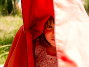 4-6 years old girl under red bath towel on meadow