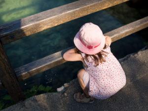 4-6 jähriges Mädchen mit Rosa Hut am Rand von einem See, blickt ins Wasser