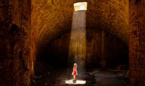 4-6 jähriges Mädchen in geringeltem Kleid im Keller im Lichtkegel stehend