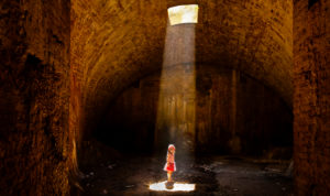 4-6 years old girl in striped dress in the cellar standing in the light cone