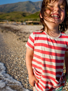 4-6 jähriges Mädchen in gestreiftem T-Shirt, lachend am Strand