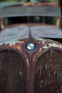 rusty cooler of an old BMW car with emblem