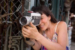 30-40 jährige Frau im Kleid an Metallgitter mit Super8 Kamera in der Hand durchschauend