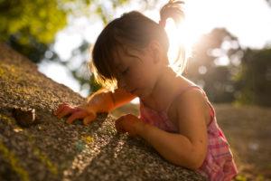 4-6 jähriges Mädchen malt mit Kreide auf graue Mauer, Sonne, Gegenlicht