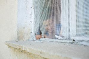 8-12 jähriger Junge hinter kaputtem Fliegengitter an einen weißen Holzfenster