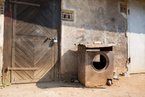 ausgebrannte Waschmaschine vor Garagentür aus Holz abgestellt