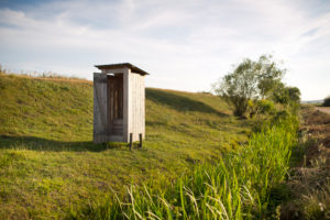 Wooden outhouse on the edge of a street on a meadow