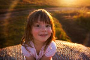 4-6 jähriges Mädchen auf Heuballen sitzend, lächelt in die Kamera, Abendlicht