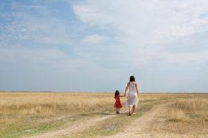 30-40 jährige Mutter mit 4-6 jährigen Kind geht Hand in Hand einen Feldweg entlang
