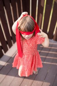 4-6 jähriges Mädchen im roten Kleid und roter Augenbinde