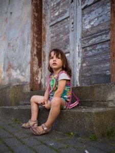 4-6 jähriges Kind mit buntem Kleid sitzt allein auf einer  Treppe vor alter Holztür