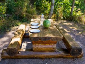 gedeckter Holztisch mit Holzbank mit drei Tellern und einer grünen Melone