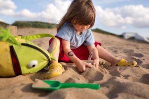 4-6 jähriges Mädchen mit roter Hose, Froschrucksack und Buddelförmchen beim Sandspielen am Strand
