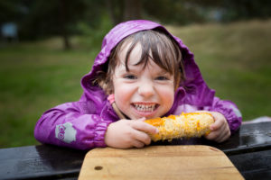 4-6 years old girl in wet purple rain jacket eating a corncob
