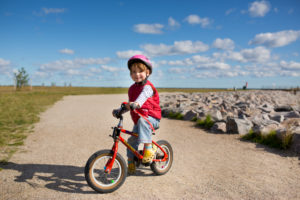 4-6 years old girl riding red children's bicycle on a way at the Baltic coast