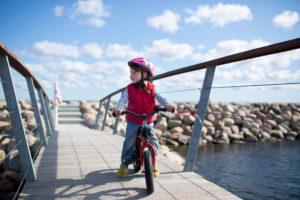 4-6 jähriges Mädchen fährt auf rotem Kinderfahrrad auf einer Brücke an der Ostseeküste