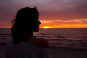 30-40 jährige Frau betrachtet Sonnenaufgang in kräftigen orangenen Farben an der Ostsee