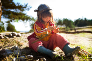 4-6 years old girl with Viking's helmet and red overalls in sand at the edge of the forest
