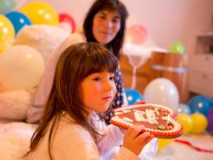 4-6 jähriges Mädchen knabbert in ihren Zimmer voller Luftballons an einem Lebkuchenherz, Mutter im Hintergrund