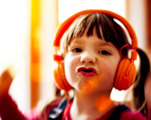 4-6 years old child dancing with orange headphones, facial play, portrait