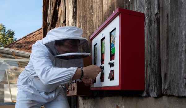Imker steht an einem Kaugummi-Automat