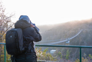 Germany, Saxony-Anhalt, Upper Harz, tourist with backpack, looks through binoculars, suspension bridge at the Rappbodetalsperre, Harz.