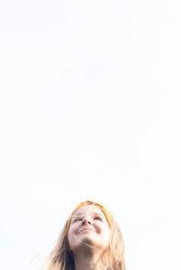 Mädchen, 8 - 12 Jahre alt, schaut lächelt nach oben, lange Haare, blond, Schülerin, weißer Hintergrund.