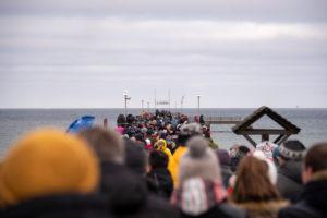 Deutschland, Mecklenburg-Vorpommern, Prerow, Hunderte Touristen stehen auf der Seebrücke und beobachten Hobbyschwimmer beim traditionellen Anbaden.