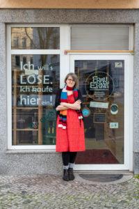 """Deutschland, Sachsen-Anhalt, Magdeburg, Sarah Werner, Inhaberin des verpackungsfreien Lebensmittelgeschäfts """"Frau Erna`s loser Lebensmittelpunkt"""", steht am Eingang ihres Unverpacktladens."""