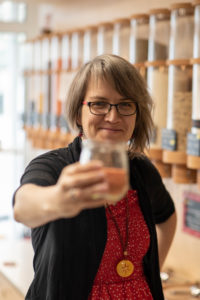 A woman holds a glass with lentils in her hand, detail from an unwrapped shop.