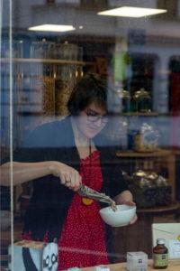 Blick durch eine Schaufensterscheibe auf ein Frau. Sie füllt Getreide in eine weiße Schüssel, Detail aus einem Unverpacktladen.