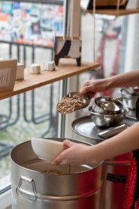 Eine Frau füllt Getreidekörner in eine weiße Schüssel, Detail aus einem Unverpacktladen.